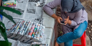 A newspaper vendor uses her smartphone while tending her stall in Jakarta, Indonesia, on Nov. 14, 2017. (Bay Ismoyo/AFP/Getty Images)